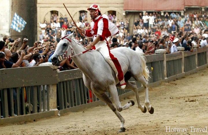 Jockey Andrea Mari of the Giraffa parish races with his horse Fedora Saura to win the Palio race in Siena